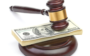 A gavel with a stack of money under it